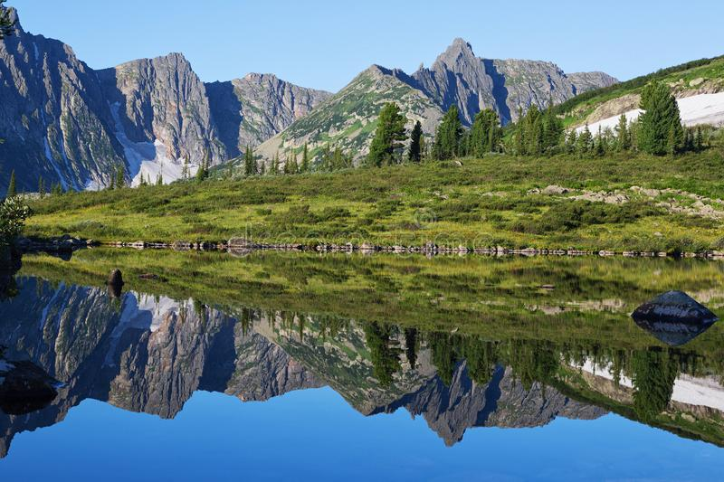 Reflection of the mountain on water, mirror image of mountains in water stock photo