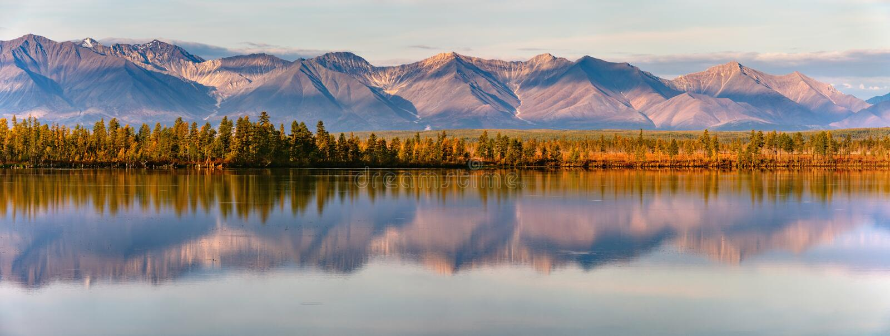 Reflection of mountains on a calm lake at sunset or sunrise. Panorama of autumn landscape in Yakutia, Sakha Republic, Russia. Beau royalty free stock image