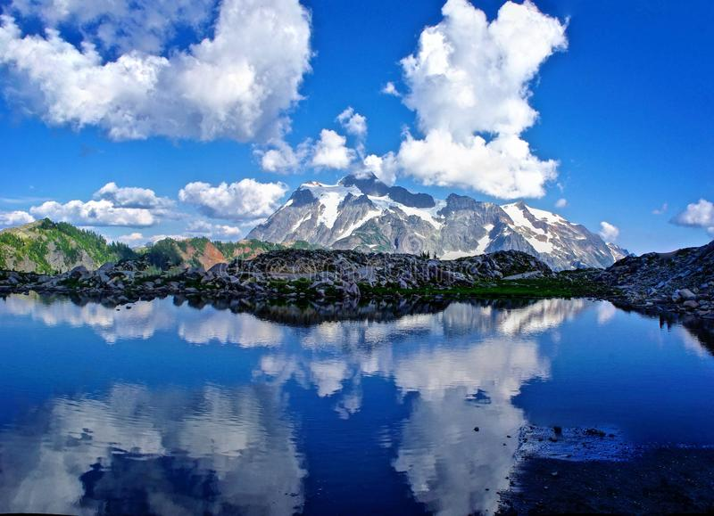 Reflection of Mountains and Clouds in Alpine Lake. Beautiful alpine lake with reflections of surrounding mountains and puffy light clouds in the clear blue water stock images