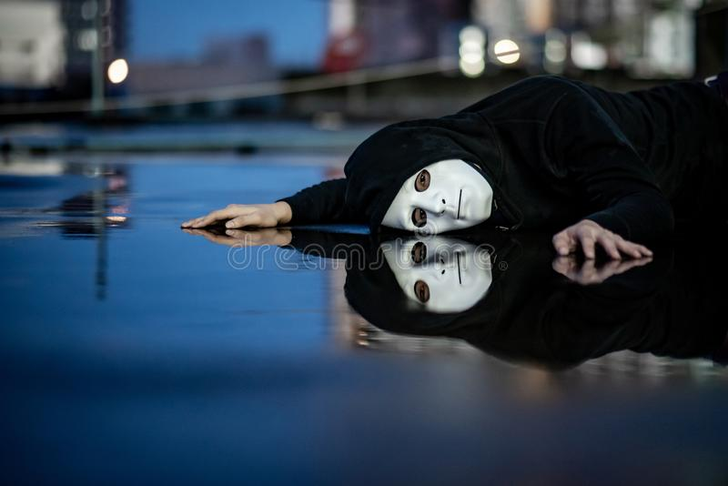 Reflection of mystery hoodie man in white mask feeling depressed and disappointed lying on wet floor after the rain. Sadness, royalty free stock image