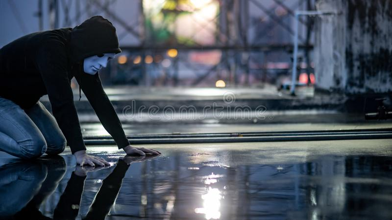 Mystery hoodie man in white mask feeling guilty. Reflection of mystery hoodie man in white mask feeling guilty looking his face on wet floor while raining stock image