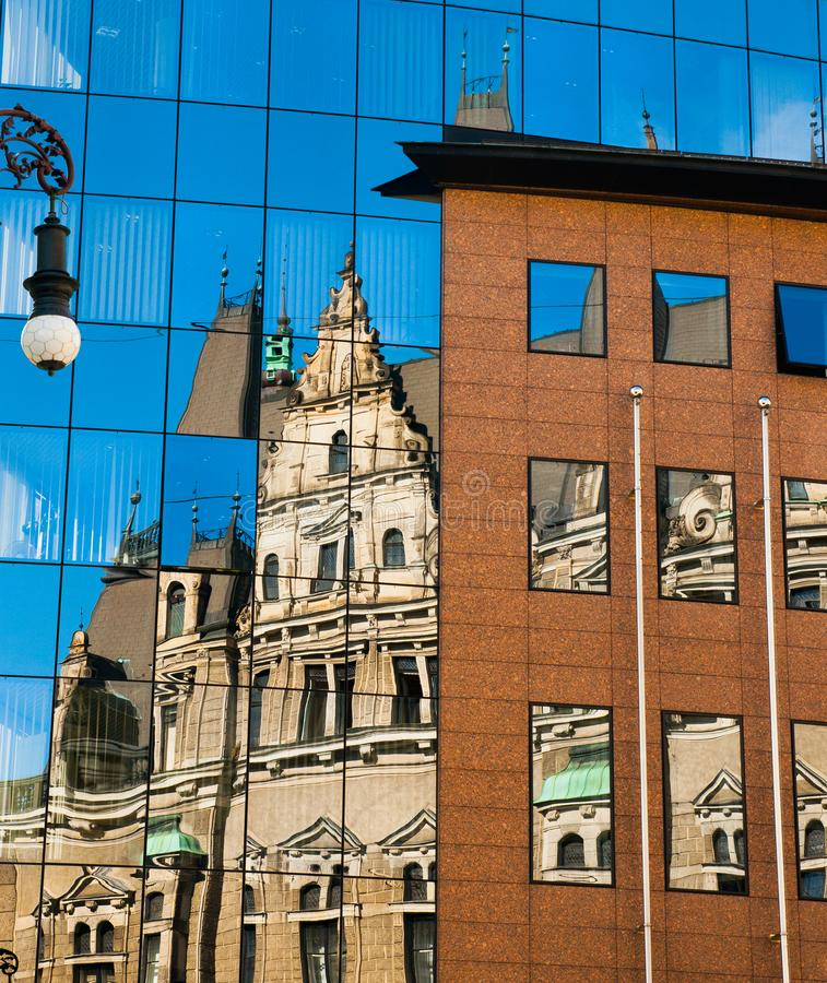 Reflection of an old building in new glass building. Old architecture versus modern reflected in glass. City of Liberec royalty free stock images