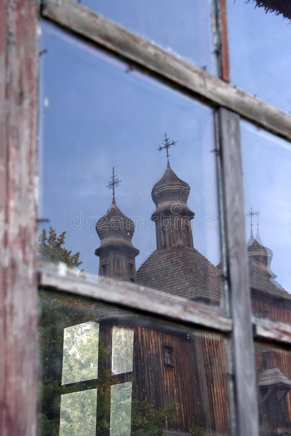 reflection of an old wooden church in a window royalty free stock photos