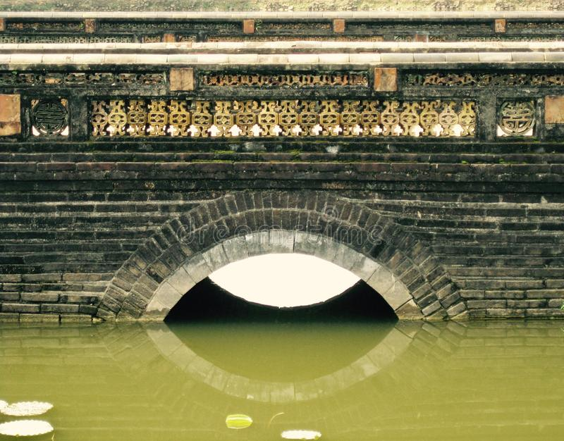 Reflection of an ornate stone and brick bridge on a lake in Vietnam stock photos