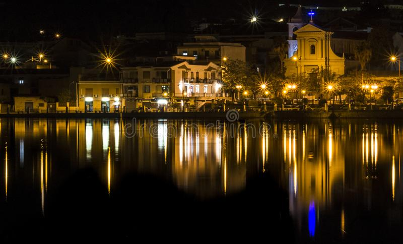 Reflection over water at night: a lake in Ganzirri Messina, Sicily. This photo was taken at night at the large lake of Ganzirri, in Messina Sicily. The image stock photo