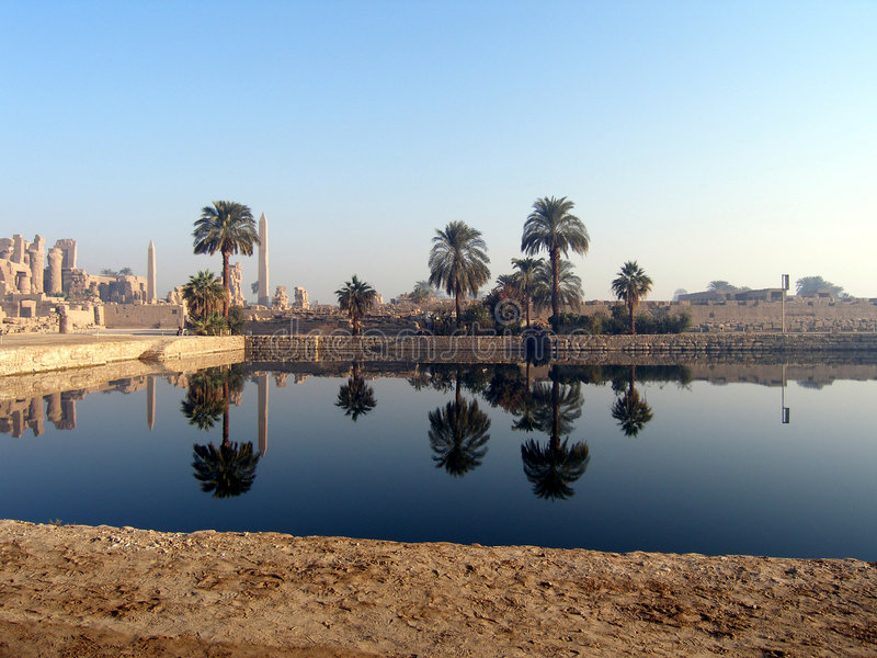 Reflection of palms. And obelisks in pool in an oasis in egypt stock image