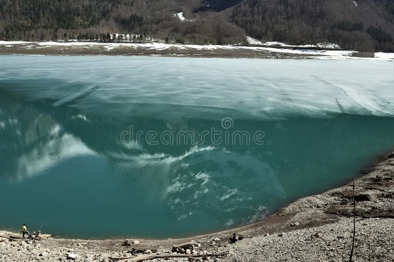 Reflection of panorama of Alps under the direct sun on the blue sky close to Klöntalersee lake. In Klöntal, Kloental valley, during sunny spring day stock photography