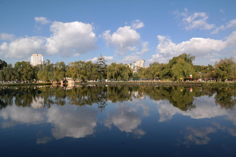 Reflection. A perfect mirrored reflection at Green Lake Kunming on a sunny blue sky day royalty free stock photography