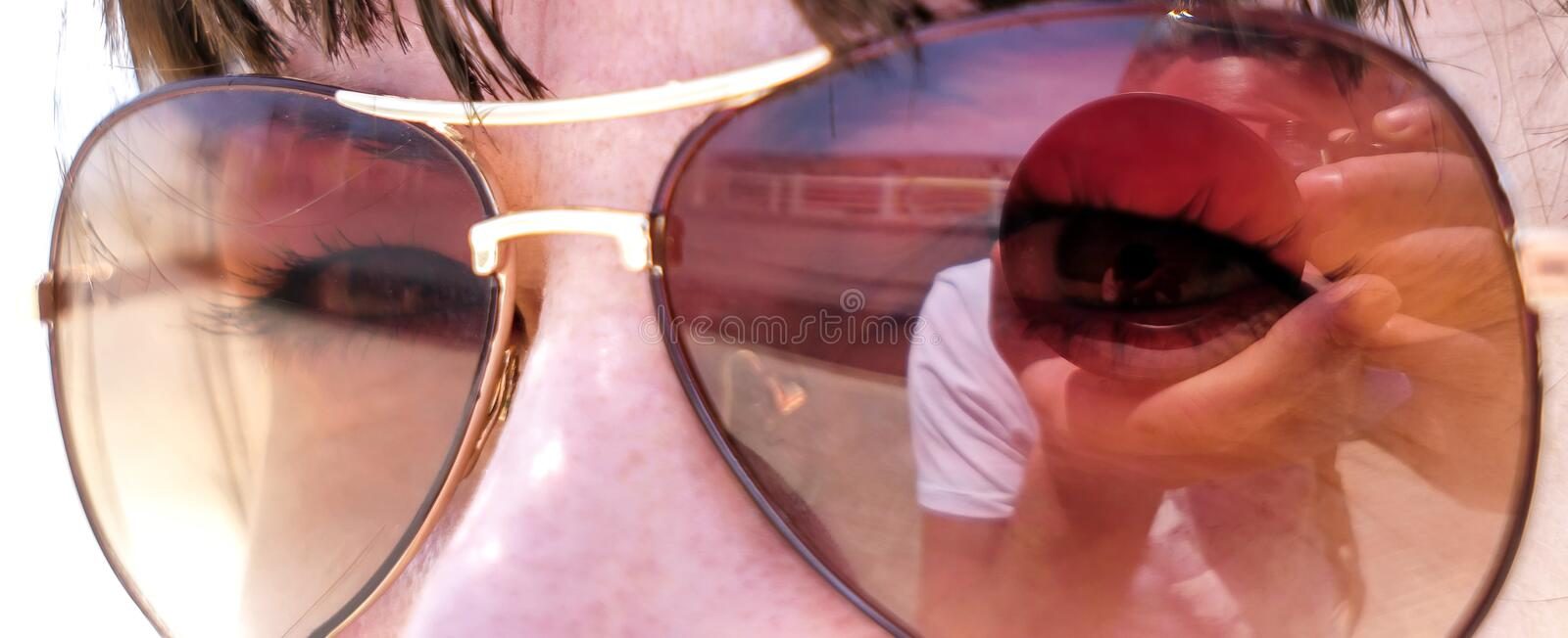 Reflection of a photographer in sunglasses of a young attractive woman, close-up stock photo