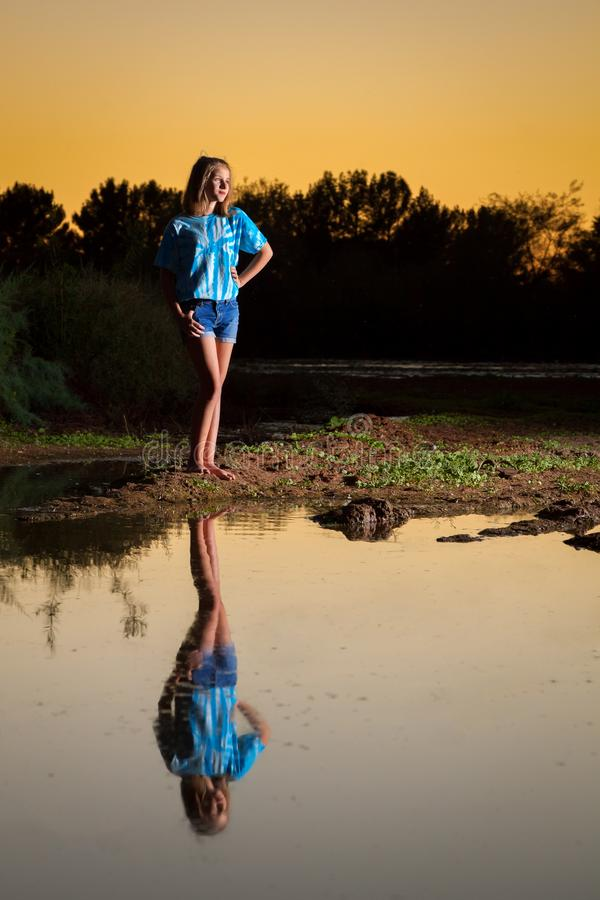 Reflection of a Preteen Girl in a Pool of Water She is Looking. Full length portrait of a preteen girl looking off into the distance by a pond at sunset. She is stock photos