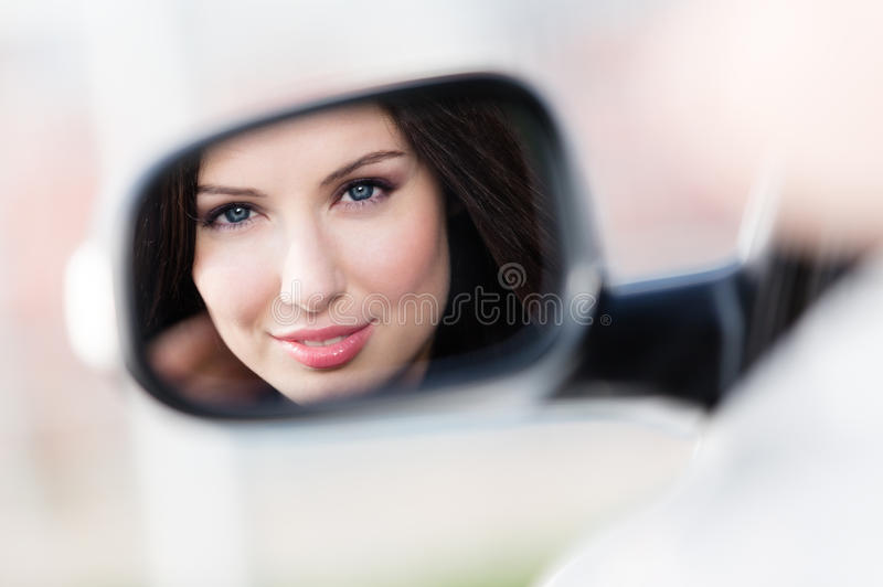 Reflection of pretty woman in the side-view mirror. Of the car that she took to have a little trip royalty free stock photo