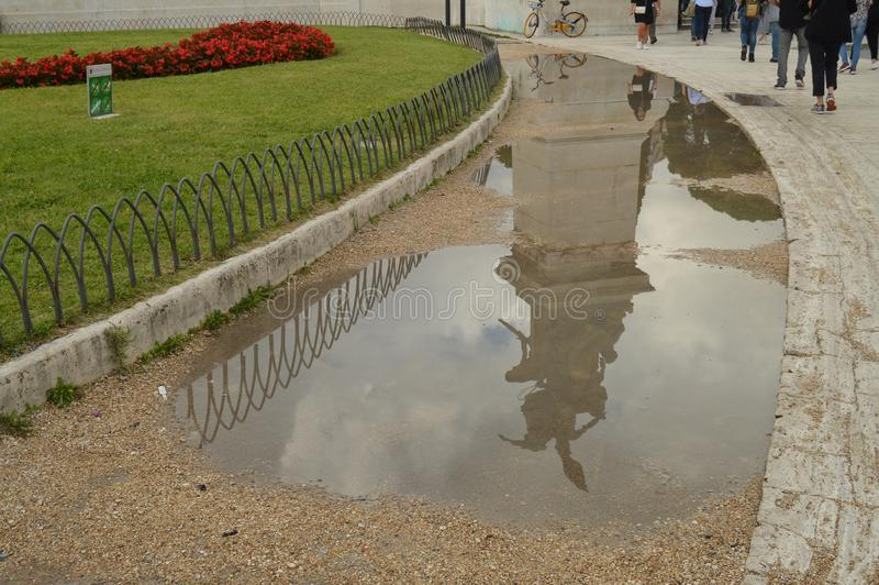 A reflection in a puddle after the rain Statue in the Vittoriano monument of Vittorio Emanuele II in Rome, Italy on royalty free stock photography