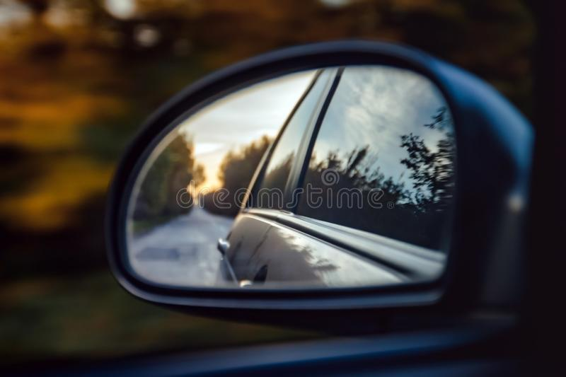 Reflection of the road in the sunset sunlight blurry in the side mirror of the car. Close-up.  stock photo