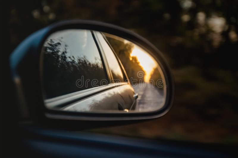 Reflection of the road in the sunset sunlight blurry in the side mirror of the car. Close-up.  royalty free stock images