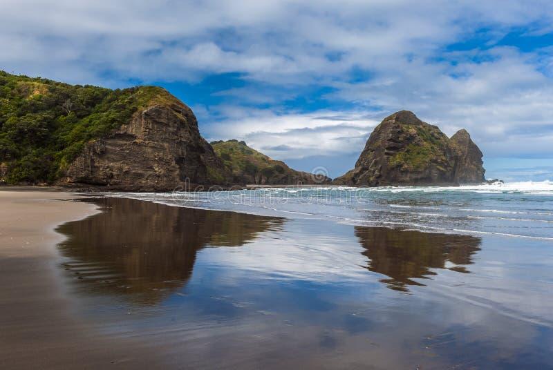 Piha beach. Reflection of rocks in the wet sand on the beautiful Piha beach near Auckland, New Zealand stock images