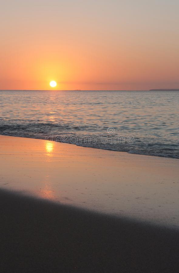 A reflection of the setting sun on the beach in Tonga. A reflection of the setting sun on the beach in Uoleva in Tonga, oceania, sand, sea, pink, vacation, blue stock image