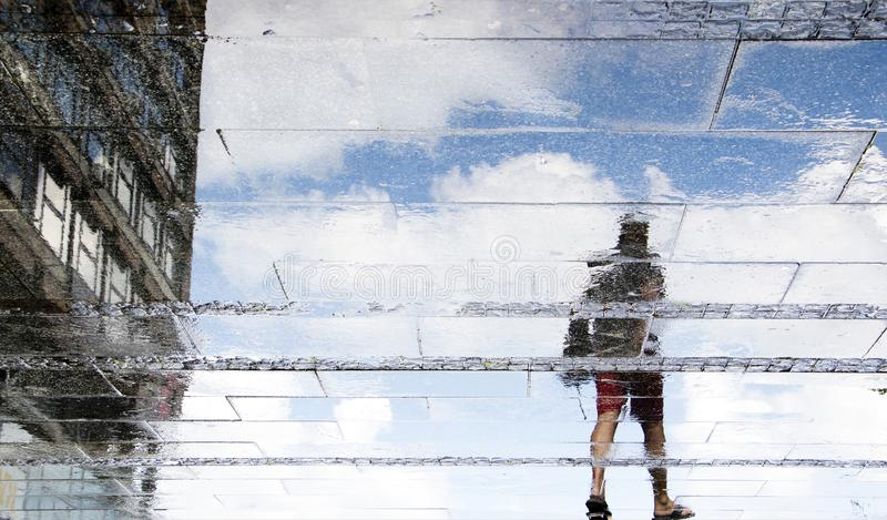 Reflection shadow silhouettes of  a young man walking on a wet street  on a sunny summer day. In the city stock photo