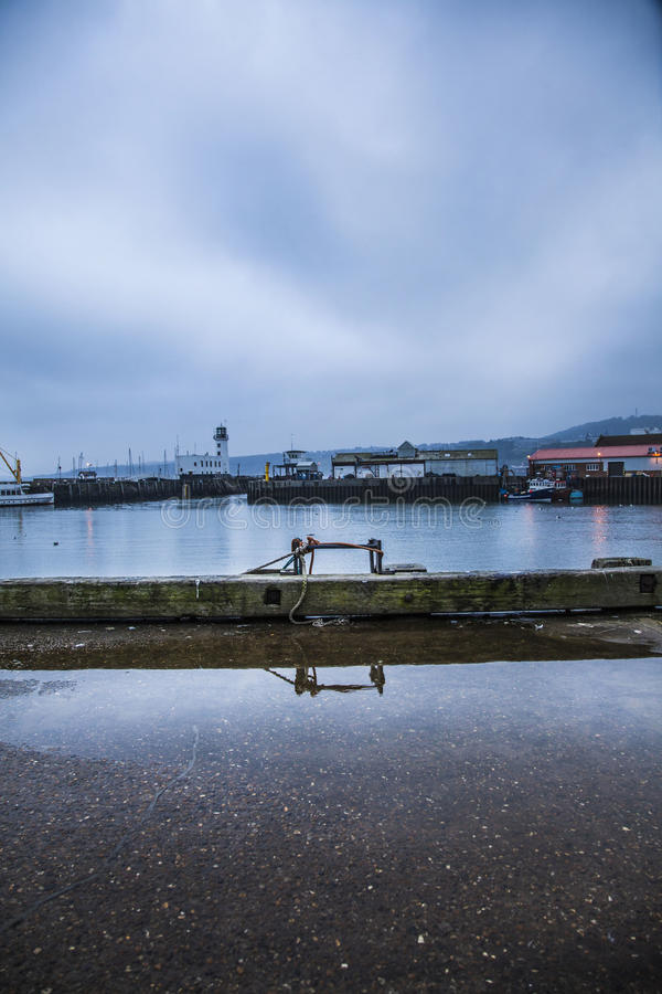 Reflection in shipping town 2. Beautiful reflection in water in cold, winter shipping town. Looking over the ocean at the fisherman's boats and lighthouses royalty free stock photo
