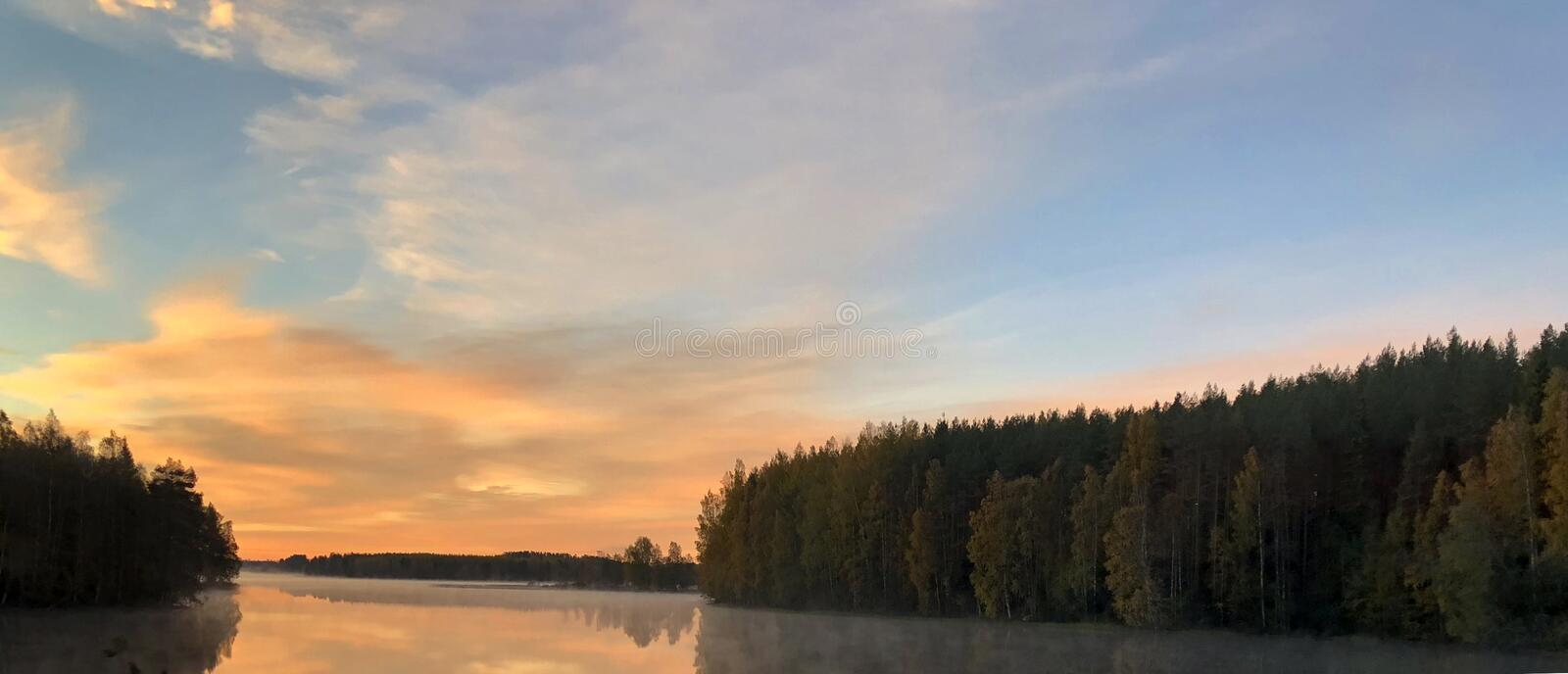 Reflection of the shore in the water and very bright fiery clouds royalty free stock photography