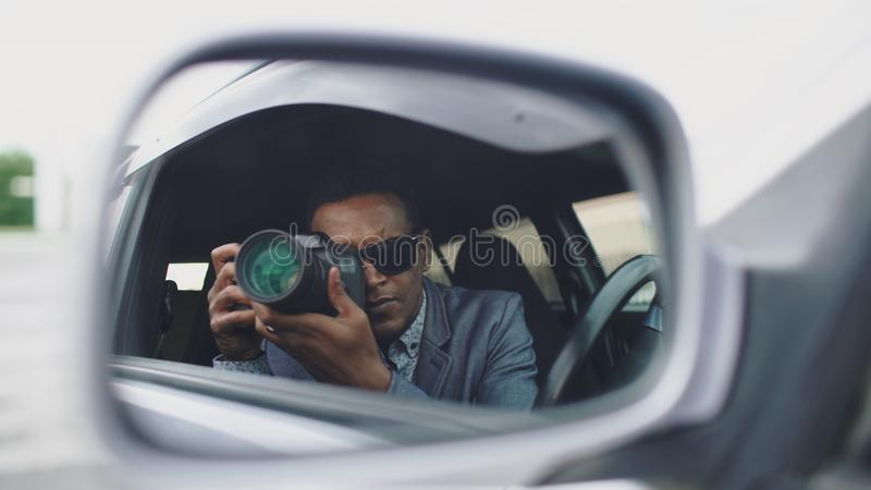 Reflection in side mirror of Paparazzi man sitting inside car and photographing with dslr camera. Reflection in side mirror of African american paparazzi man stock images