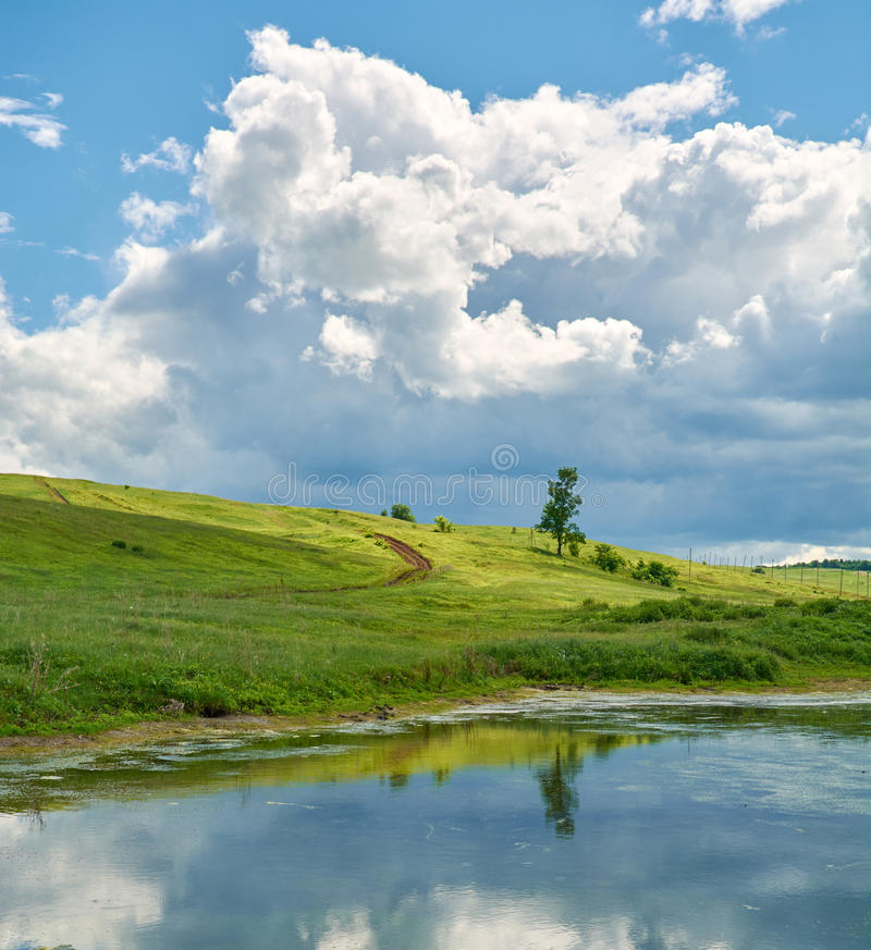 Reflection of the sky with clouds in the water near the green hill. Reflection of the sky with clouds in a pond near a green hill on a summer day royalty free stock images