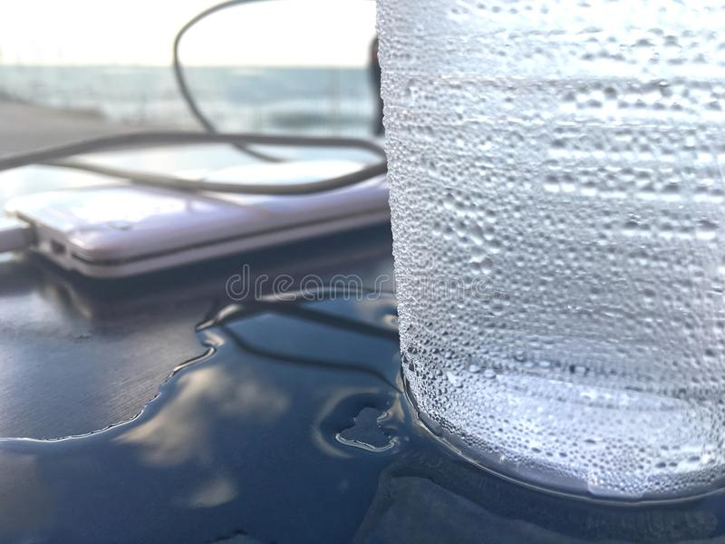 Reflection of the sky and a misted glass with cold water on a table. Blurred image of the powerbank with a wire connected to it to charge the smartphone on the stock photography