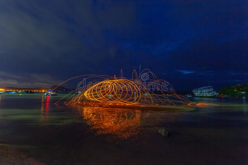 reflection of spark fire swirl from steel wool with long exposure speed motion abstract at sunrise royalty free stock photo