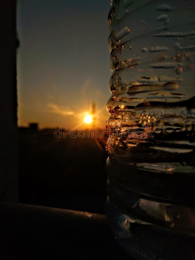 Reflection of Sun on a Bootle. Evening sunset seen through the reflection of bottle stock photography