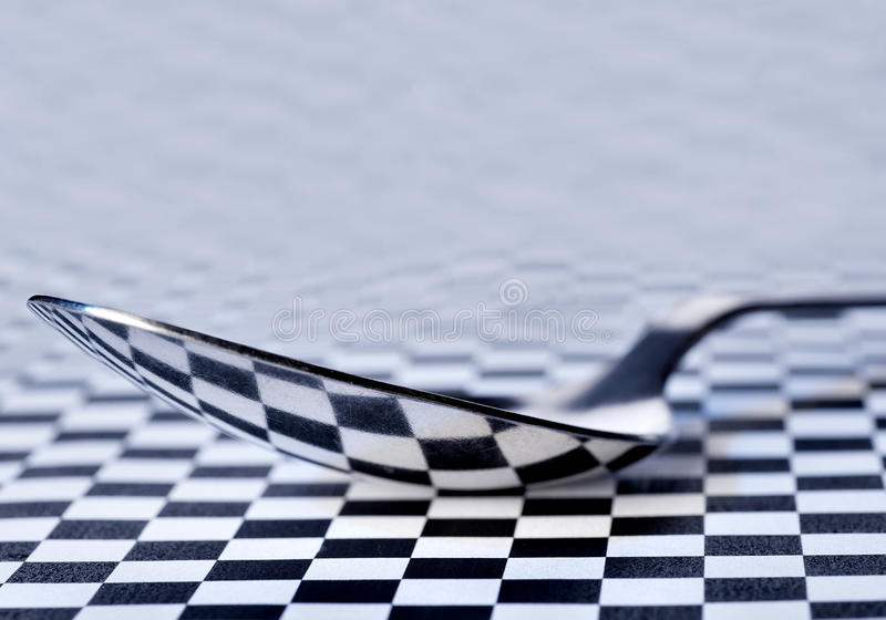 Reflection in a tablespoon. Reflection of a chess field in a tablespoon royalty free stock photos
