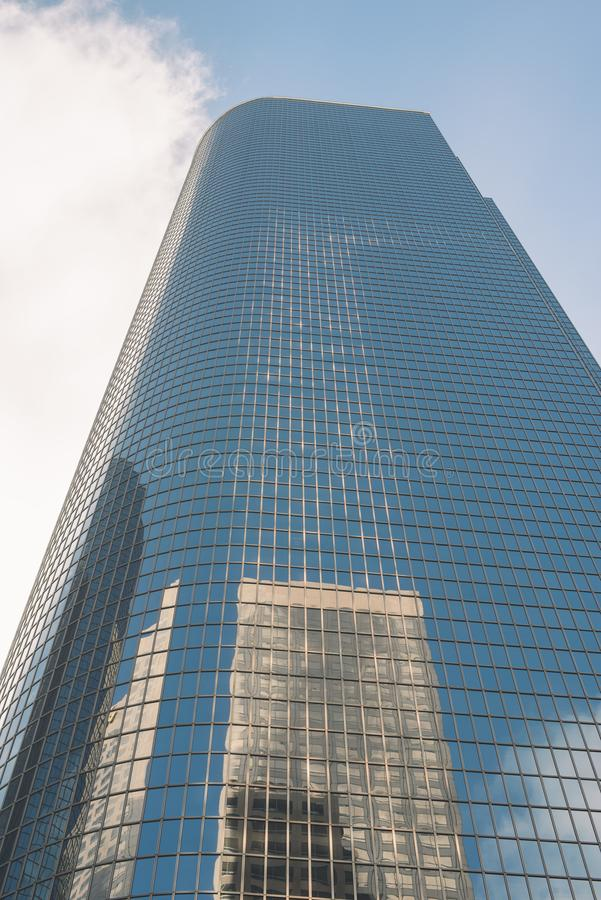 Reflection of a Tall Building on a Glass Sky Scraper. A tall glass sky scraper with reflections and blue sky stock photography