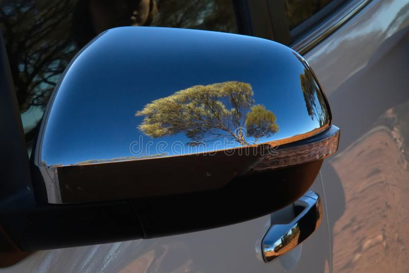 Reflection of tree in car wing mirror in Australian outback. Image of tree reflected in polished wing mirror of car in the Australian outback royalty free stock photography