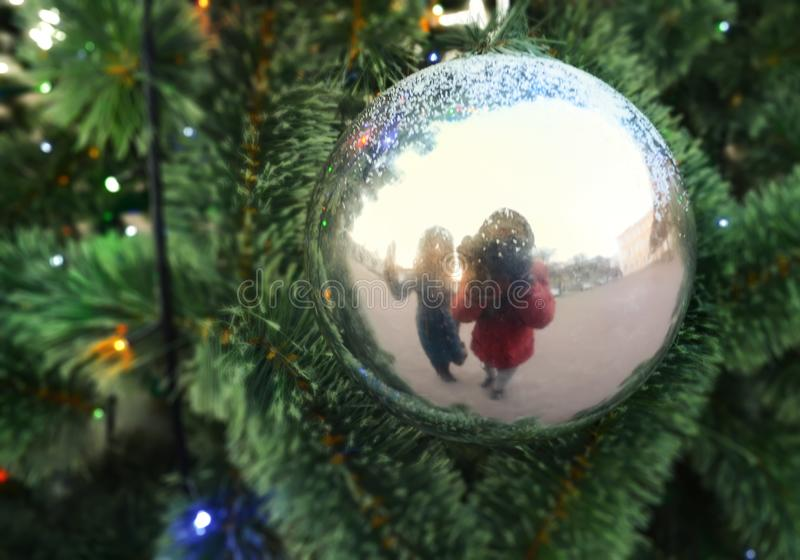 Reflection of two human figures in the Christmas ball on the branches of artificial fir royalty free stock photo