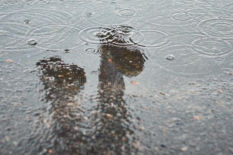 Reflection of two rainboots in a puddle at rainy day stock photo