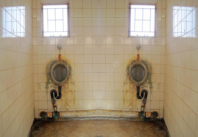 REFLECTION OF A URINAL IN A CORNER. View of a duplication of a bathroom in a deteriorated state showing signs of ruin and decay royalty free stock photo