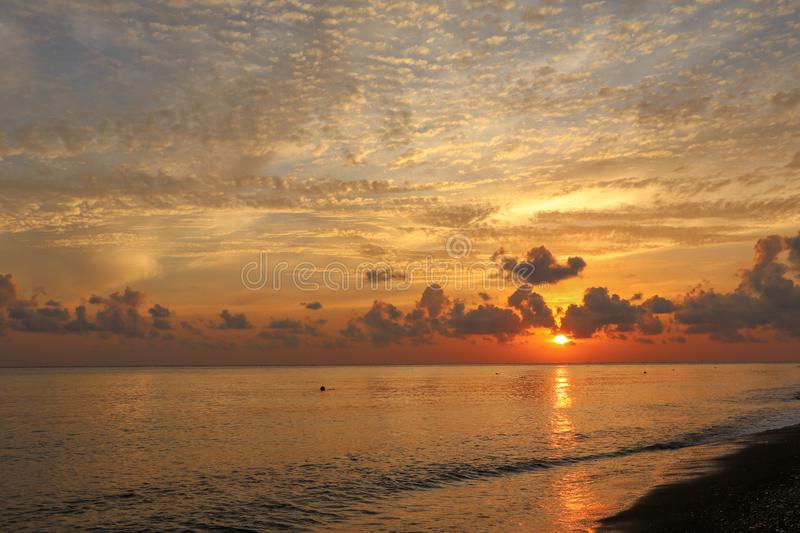 Reflection of vivid sunset sky over sea. Colorful sunrise with clouds over ocean. Beautiful nature background - orange sunset. stock photos