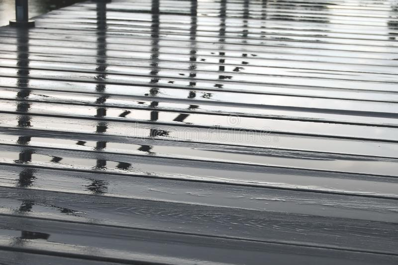 Reflection in water on wooden pedestrian flooring on rainy day royalty free stock photography