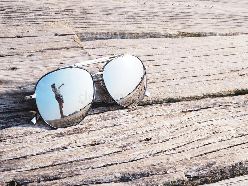 Reflection of woman hand pointing upward to blue sky in sunglasses stock photos