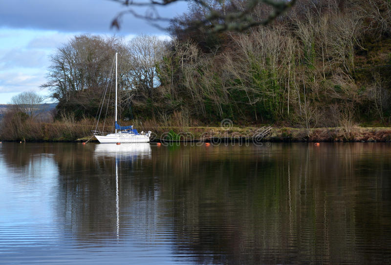 Reflection of yacht moored in Loch in Scotland. Yacht with water reflection moored in a quiet loch in the Western Isles of Scotland stock photos
