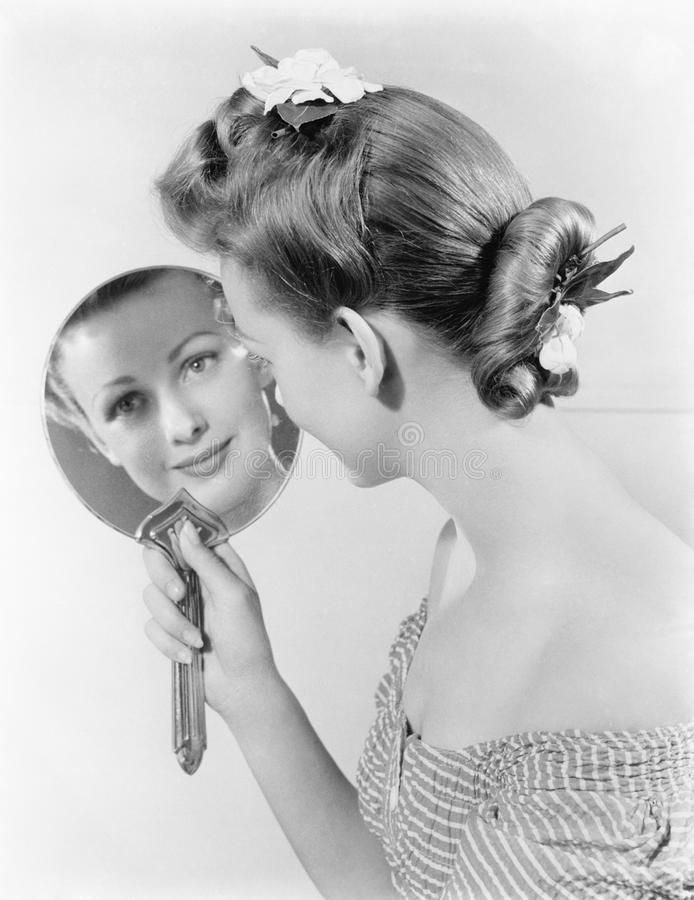 Reflection of a young woman, looking in a mirror stock images