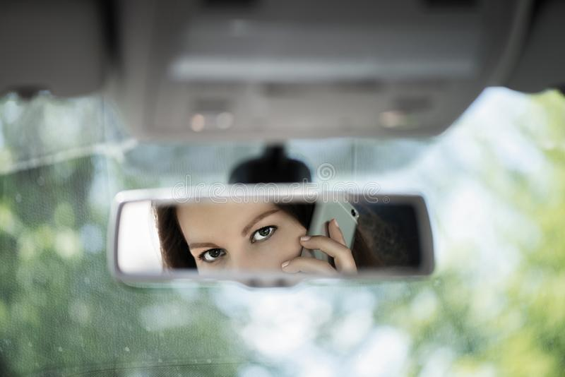 Reflection of young woman talking on a mobile phone in the car rear view mirror. No cell phone, while driving. Safe driving concept royalty free stock photos