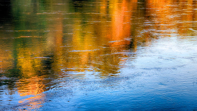 Reflections of Autumn on a flowing river stock images