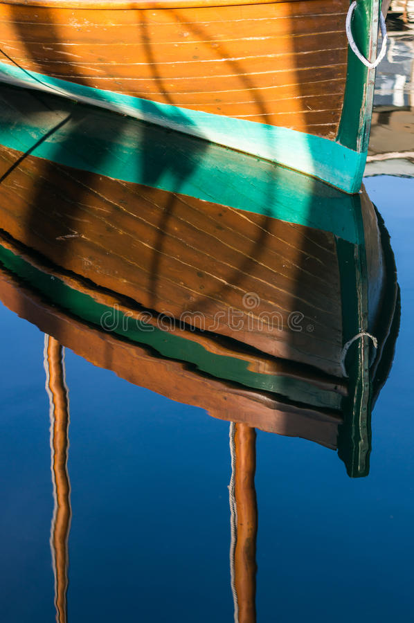 Reflections of a beautiful wood boat in the sun. stock photography