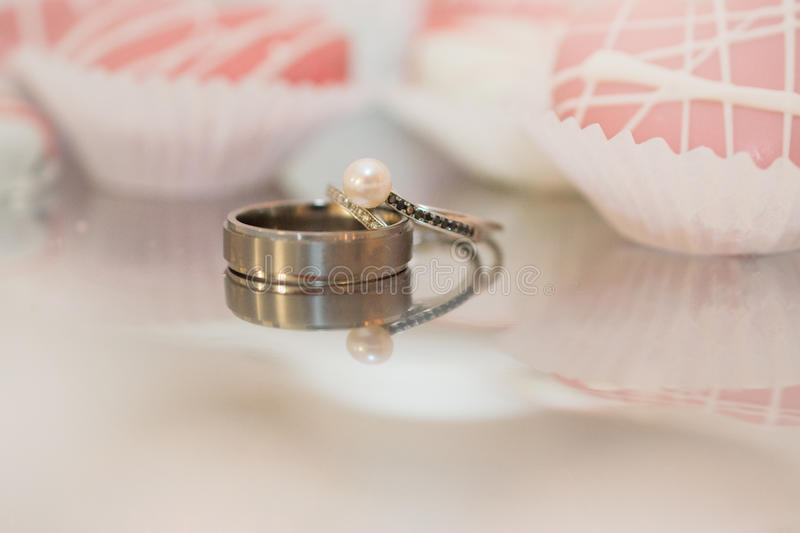Reflections of Bride and Grooms rings. A reflection of bride and grooms rings on a sliver platter, with pink heart cookies in the background royalty free stock photo