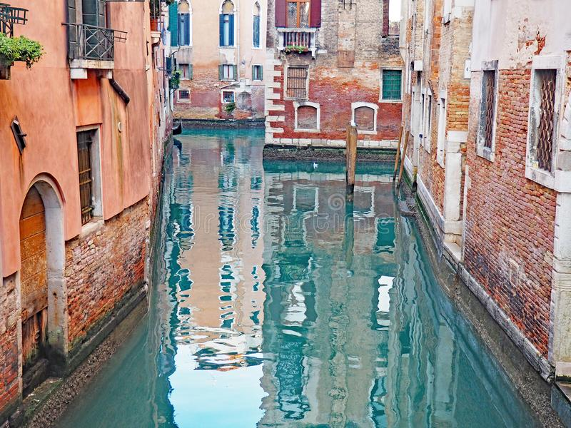 Reflections in a canal in the city of Venice, Italy. Colorful buildings reflect in a typical canal located in the city of Venice, Italy royalty free stock image