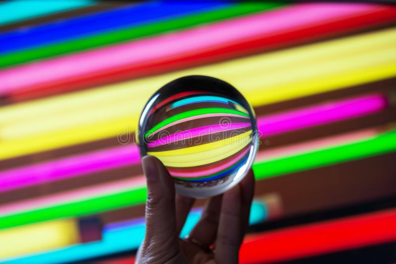 Reflections of colorful neons in a crystal ball. Astract colorful stock image