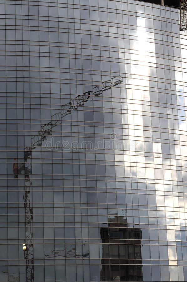 Reflections of crane at building site, milan. Foreshortening of construction site of modern, glass covered, building in city center, shot from the street under stock image