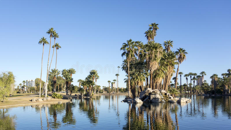 Reflections in Encanto Park Lake, Phoenix, AZ. Bright and clear winter sky reflecting in deep blue water of Encanto park lake, Phoenix downtown, Arizona stock image