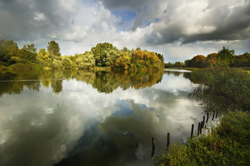 Reflections in the lake. A picture of clouds reflecting in one of the small lakes of the Delftse Hout, a park close to the City of Delft in the Netherlands royalty free stock photography