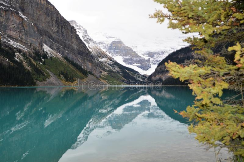 Reflections on Lake Louise, Canada. Mountains looming over Lake Louise in Canada in the fall after new snowfall stock photos