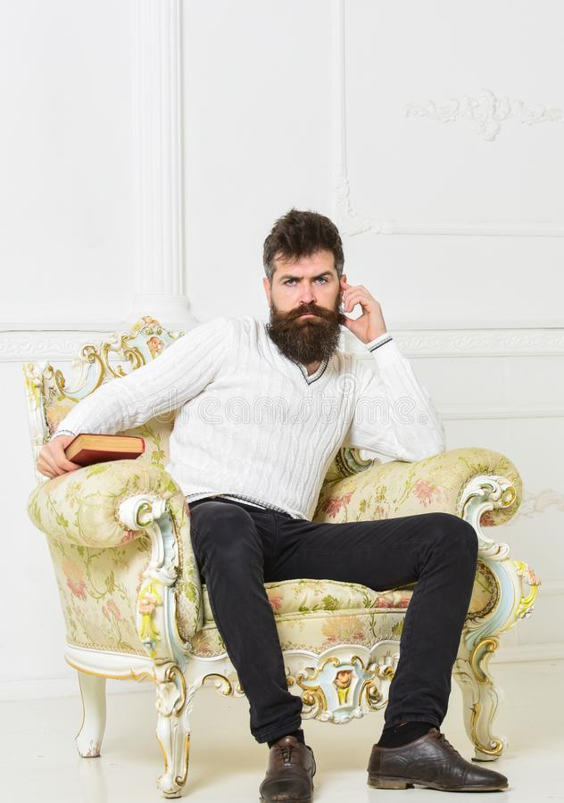 Reflections on literature concept. Connoisseur on thoughtful face finished reading book. Man with beard and mustache. Sits on armchair, holds book, white wall royalty free stock photos
